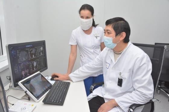 Двое врачей сидят возле монитора