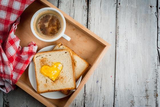 Чашка кофе и хлеб с яйцом в виде сердечка на подносе