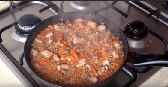 Гречневая каша с мясом и морковью томится на сковороде