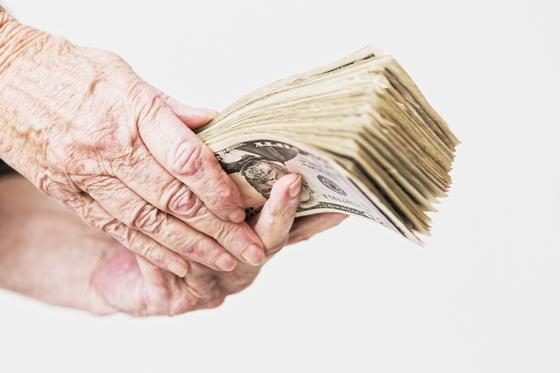 Пенсионерка держит в руках много денег