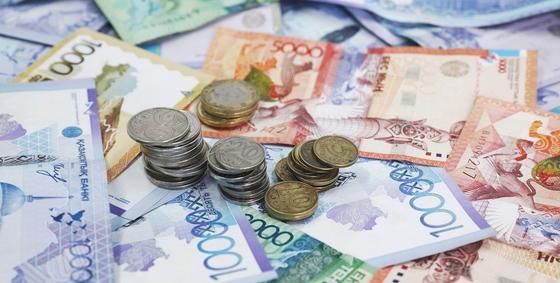 Монеты лежат на купюрах тенге