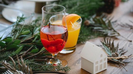 Среди зеленых веточек на столе бокал с вишневым компотом, стакан с апельсиновым соком