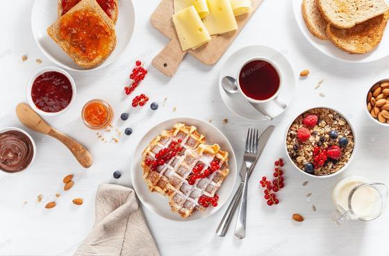 Вафли на тарелке, рядом чай, варенье
