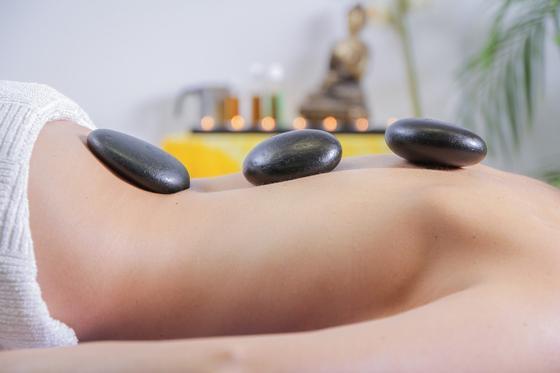 Девушка лежит с камнями на спине (массаж)