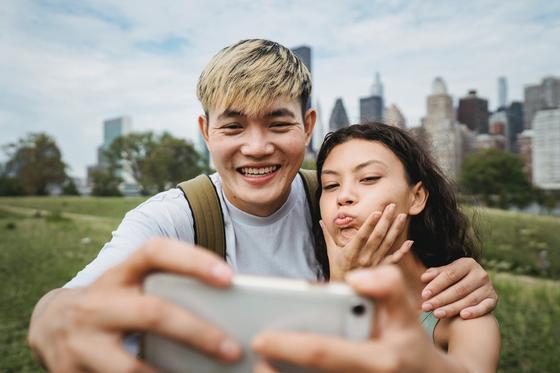 Парень и девушка делают селфи на фоне города
