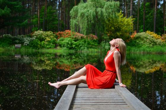 Девушка сидит на берегу пруда