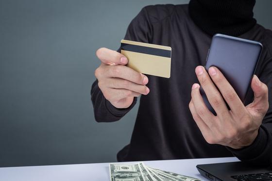 Мужчина держит смартфон и банковскую карту
