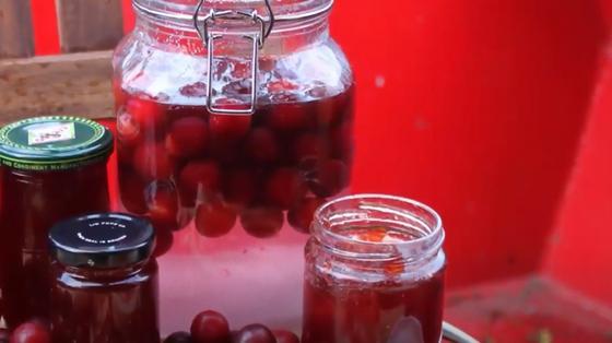 На столе банка с компотом из красных черешен и маленькие банки с вареньем