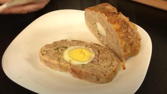Кусочки говяжьего рулета с целым яйцом на тарелке