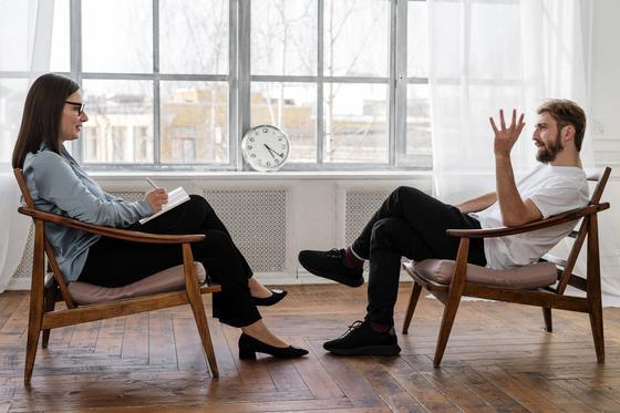 Мужчина и женщина общаются, сидя в креслах друг напротив друга