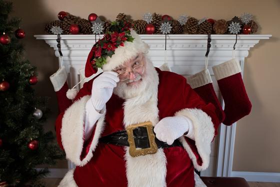 Санта-Клаус сидит возле камина и елки