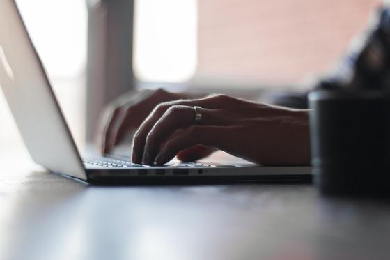 Мужчина печатает на ноутбуке