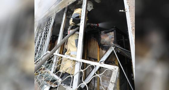 Пожарный тушит огонь, стоя в окне здания