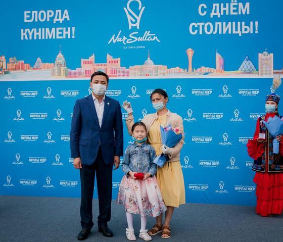 Алтай Кульгинов стоит рядом с женщиной и ребенком