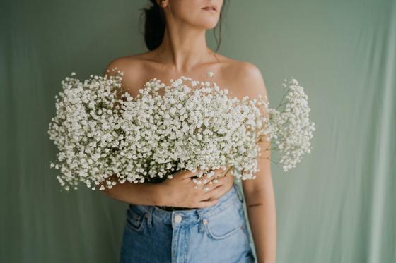 Девушка в джинсах с букетом цветов