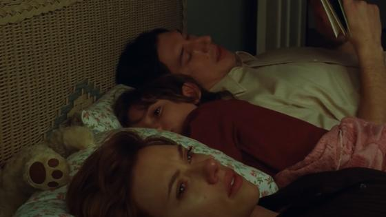 Женщина, мальчик и мужчина лежат в кровати, мужчина читает малышу книжку