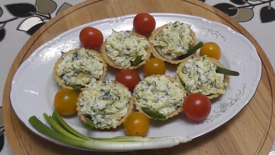 Тарталетки с начинкой из селедки на тарелке с помидорами