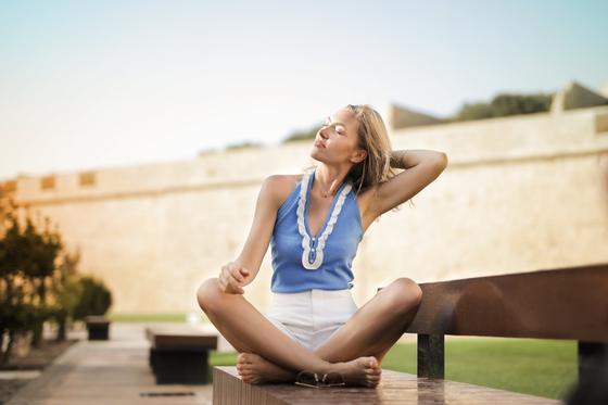 Женщина сидит в позе лотоса на улице
