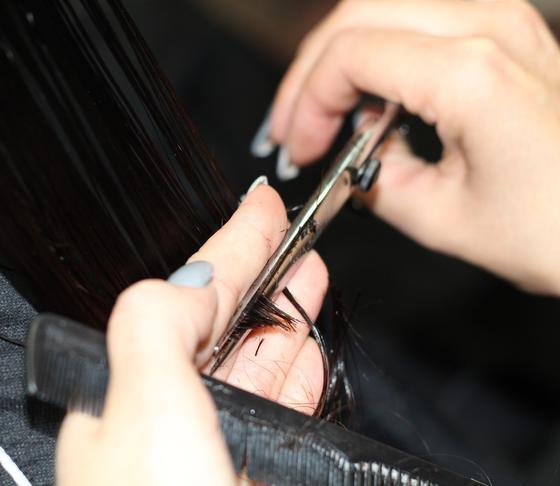 Парикмахер стрижет волосы