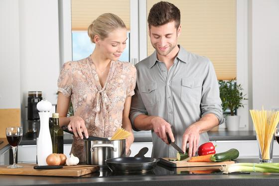 Пара вместе готовит еду