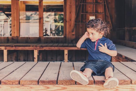 Мальчик сидит на деревянном мосту