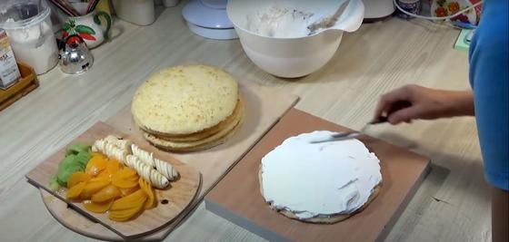 Крем намазывают на корж торта  на фоне фруктов для его украшения