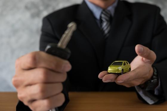 Ключ и модель машины в руках