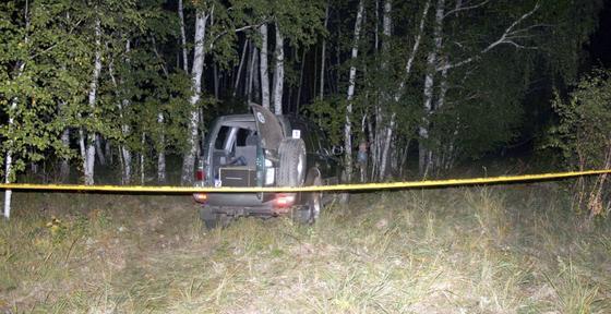 Машина стоит в лесу за желтой лентой