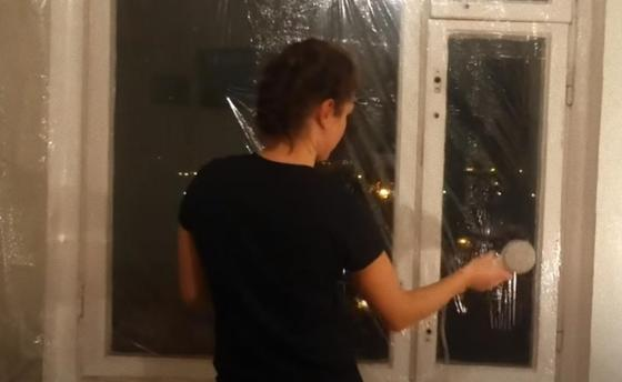Женщина утепляет окно термопленкой