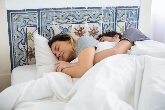 Женщина и мужчина, обнявшись, спят в кровати