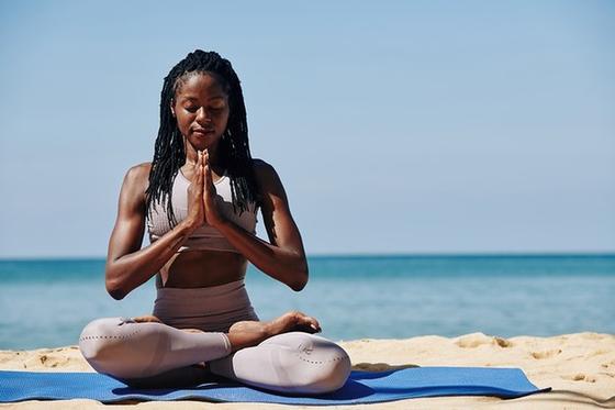 Девушка медитирует в позе лотоса на берегу моря