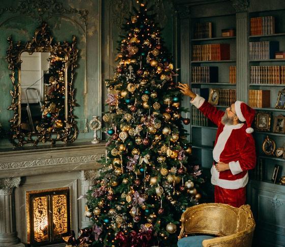 Наряженная елка и человек в костюме Санта-Клауса возле нее