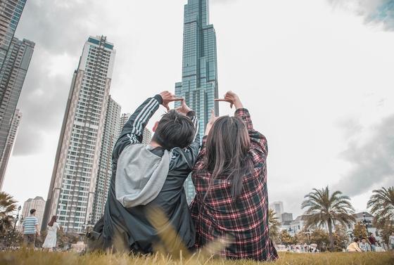 Юноша и девушка смотрят на высотки в мегаполисе