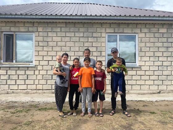 Семья переселенцев стоит возле своего дома