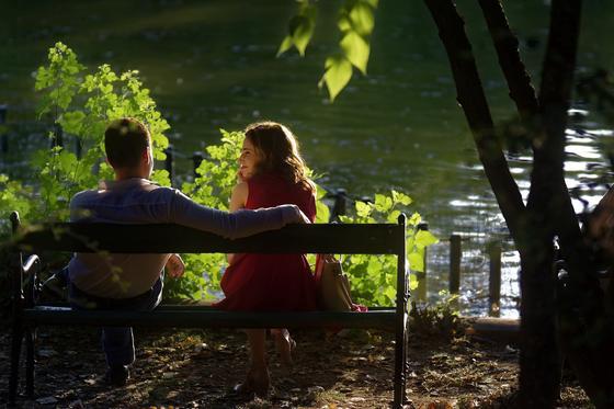 Парень и девушка сидят на скамье