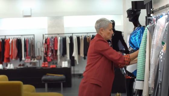 Лилия Рах в бутике рассматривает одежду