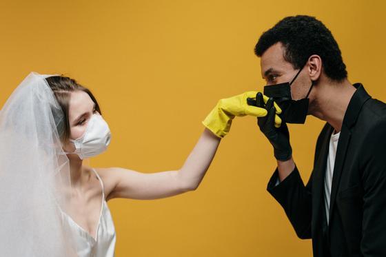 Жених в маске целует руку невесты