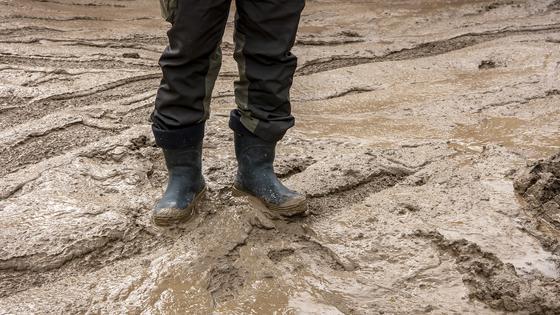 Мужчина стоит на улице в грязи