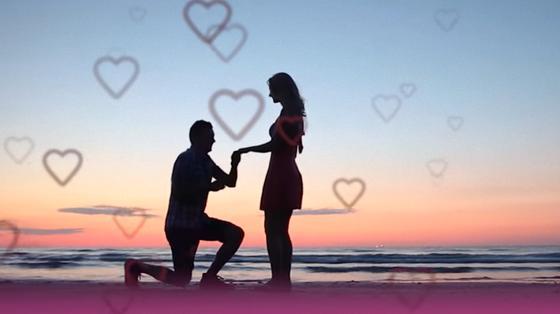 На берегу моря силуэт парня, стоящего на коленях и держащего девушку за руку