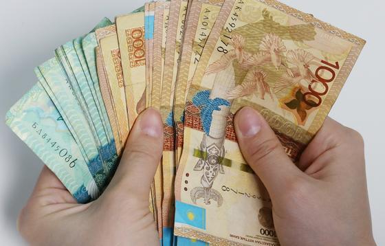 Человек держит в руках пачку денег