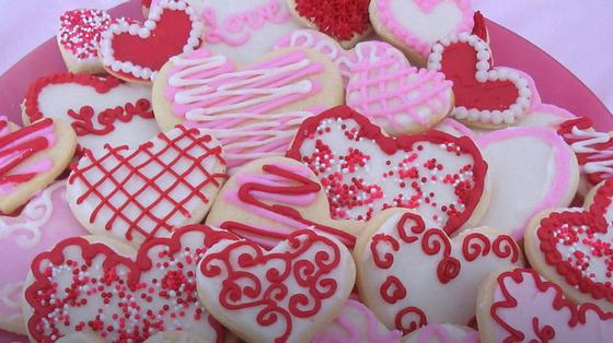 На столе лежит много печенья в форме сердца, покрытые глазурью и красивыми узорами сверху