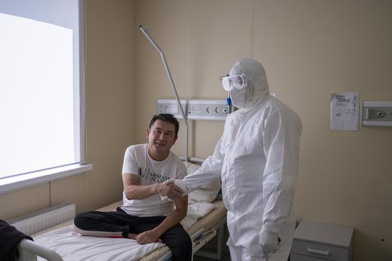Мужчина сидит на кровати в больнице