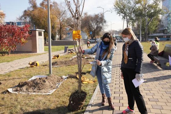 Две девушки стоят возле дерева