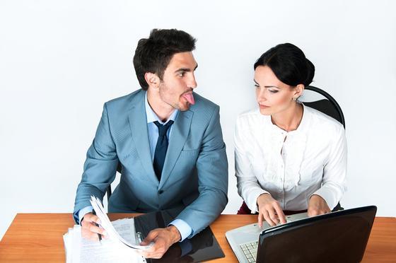 Мужчина показывает язык коллеге