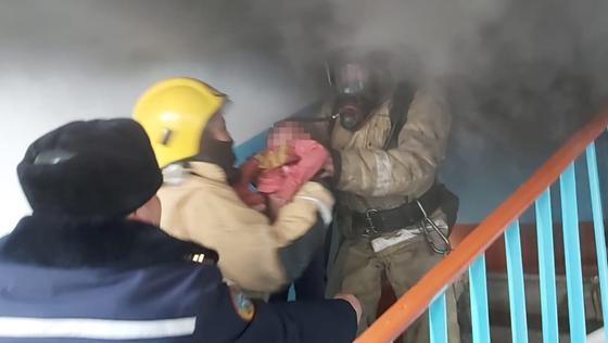 Спасатели выносят ребенка из дома по лестнице