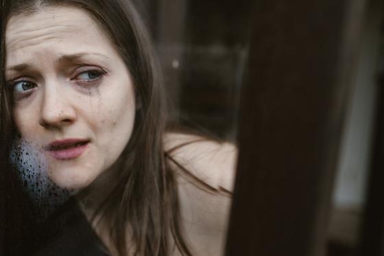 Расстроенная девушка с заплаканным лицом стоит у окна