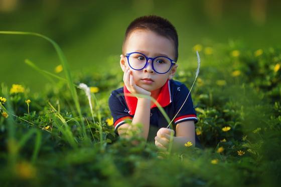 Мальчик лежит в траве