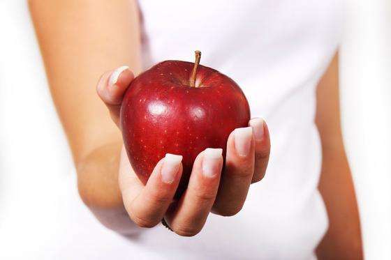 Девушка держит красное яблоко