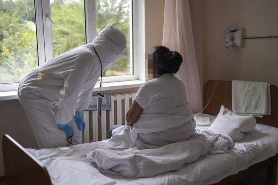 Женщина сидит на кровати в больнице