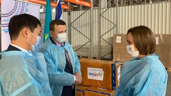 Люди в защитных костюмах стоят возле коробок